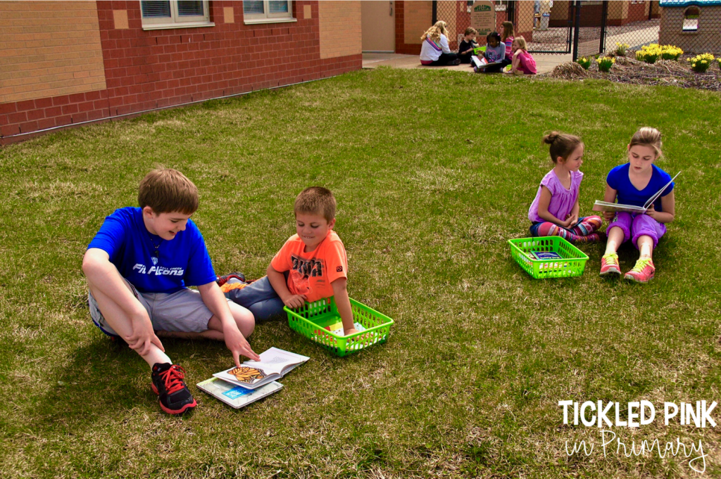 students reading with a partner sitting in the grass