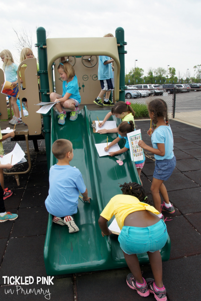 students on a playground doing work on clipboards