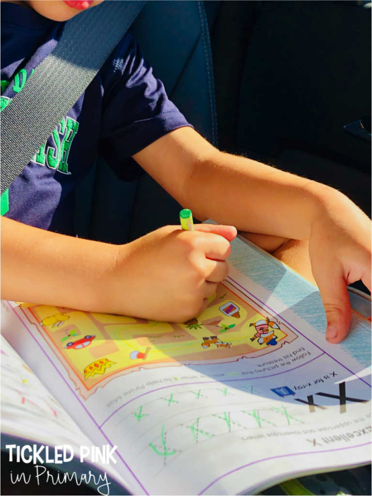 kid working on my kindergarten workbook in the car