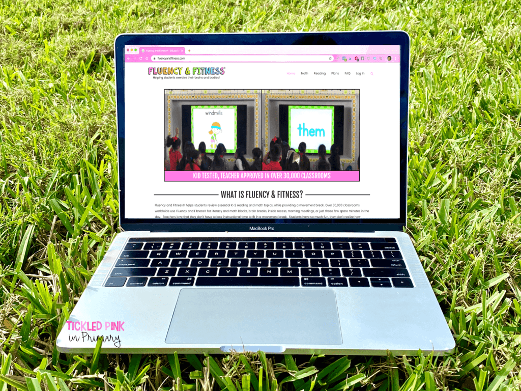computer in the grass showing the Fluency & Fitness website as outdoor learning activities