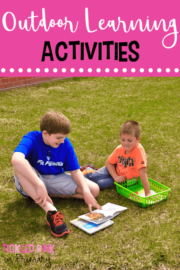 2 kids reading a book in the grass for outdoor learning activities